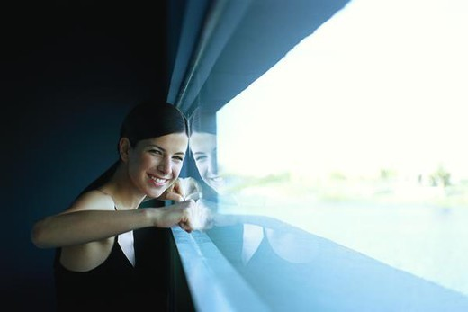 Stock Photo: 4276-9077 Woman pressing fists against window, smiling at camera