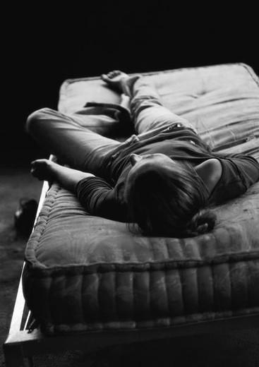 Stock Photo: 4276-9101 Woman lying on back on bare mattress