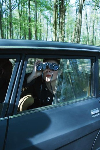 Woman sitting in car, looking out window through binoculars : Stock Photo