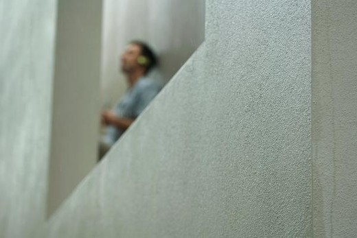 Man leaning against wall, focus on concrete in foreground : Stock Photo