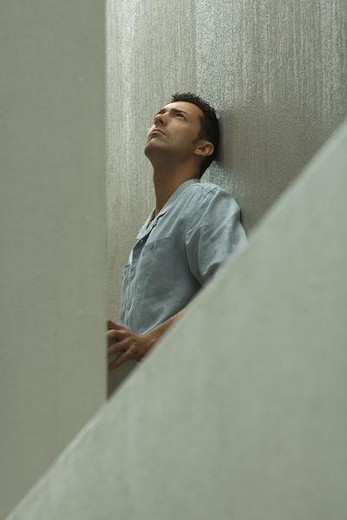 Stock Photo: 4276-9178 Man sitting outdoors in rain, leaning against wall, looking up