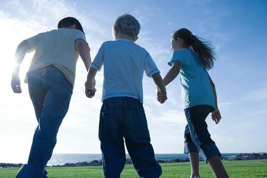 Three children walking across grass, holding hands, low angle view : Stock Photo