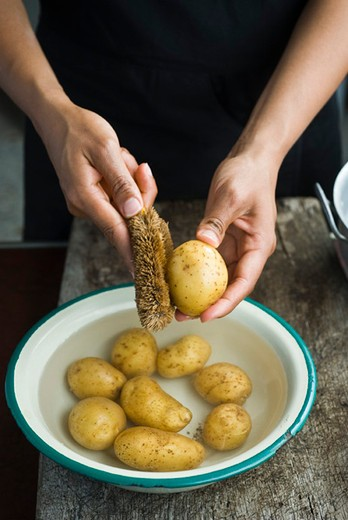 Scrubbing baby potatoes : Stock Photo