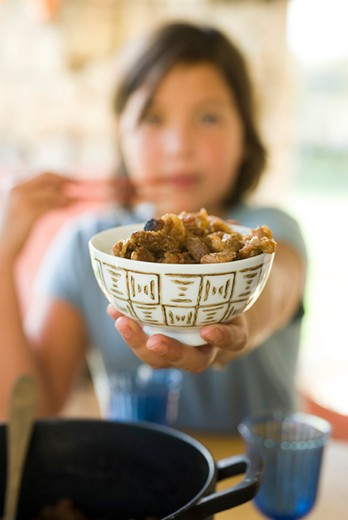 Stock Photo: 4277-1463 Girl holding out bowl of cooked food
