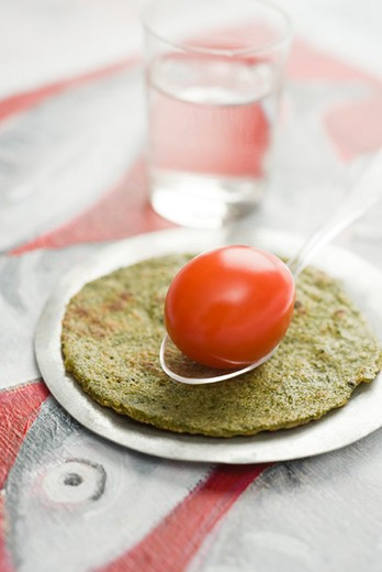 Savory spiced crepes topped with cherry tomato : Stock Photo