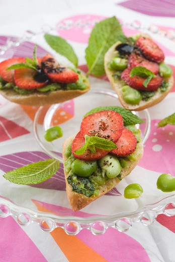 Broad bean and strawberry toasts : Stock Photo