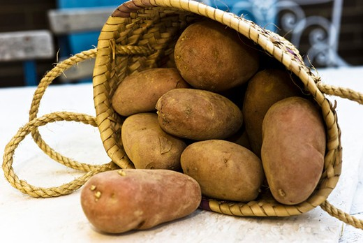 Raw potatoes spilling out of basket : Stock Photo