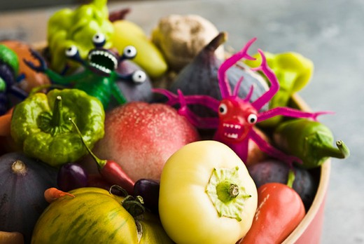 Stock Photo: 4277-2180 Fresh vegetables and fruit in bowl with plastic monster toys