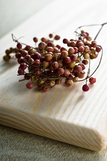 Red peppercorns on cutting board : Stock Photo