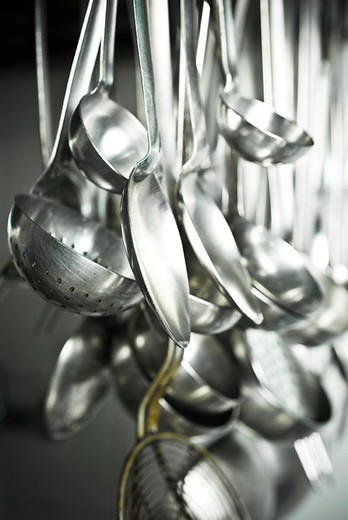 Cooking utensils hanging in kitchen : Stock Photo