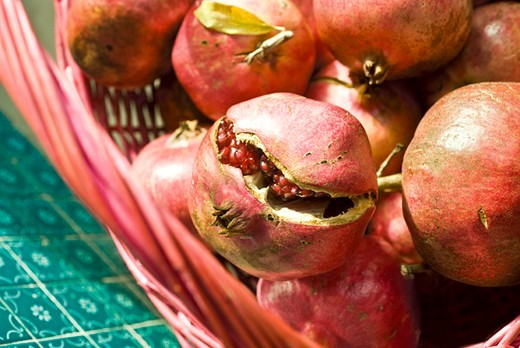 Stock Photo: 4277-2270 Ripe pomegranates in basket, one cracked open revealing seeds