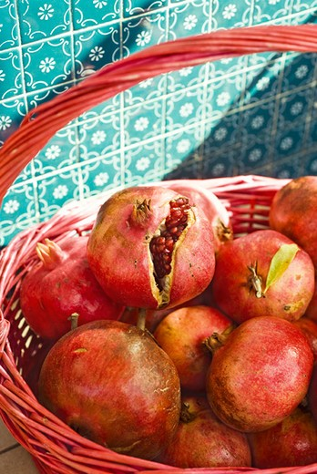 Ripe pomegranates in basket, one cracked open revealing seeds : Stock Photo