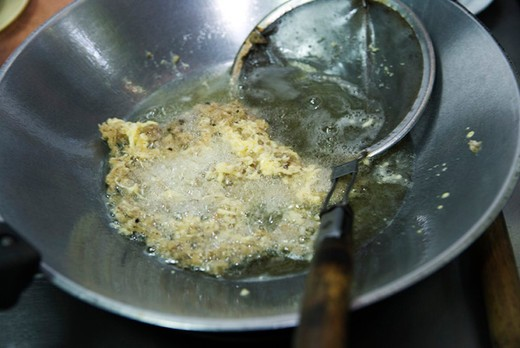 Preparing fish fritters, frying fish in coconut oil : Stock Photo