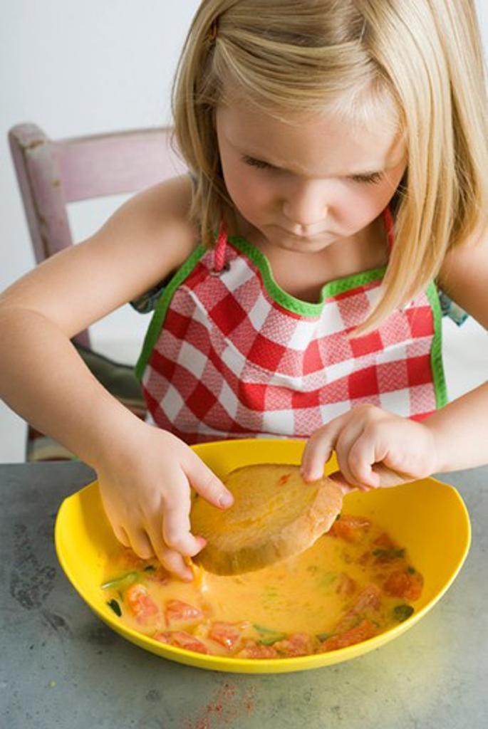 Stock Photo: 4277-2597 Little girl dipping bread in egg batter