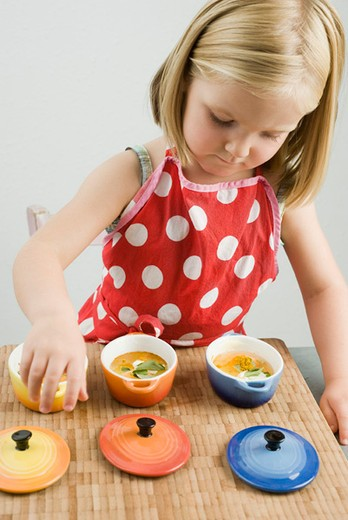 Stock Photo: 4277-2604 Little girl preparing baked eggs in small casserole dishes