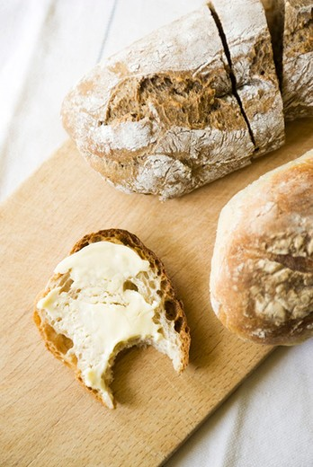 Fresh bread, buttered slice with missing bite : Stock Photo
