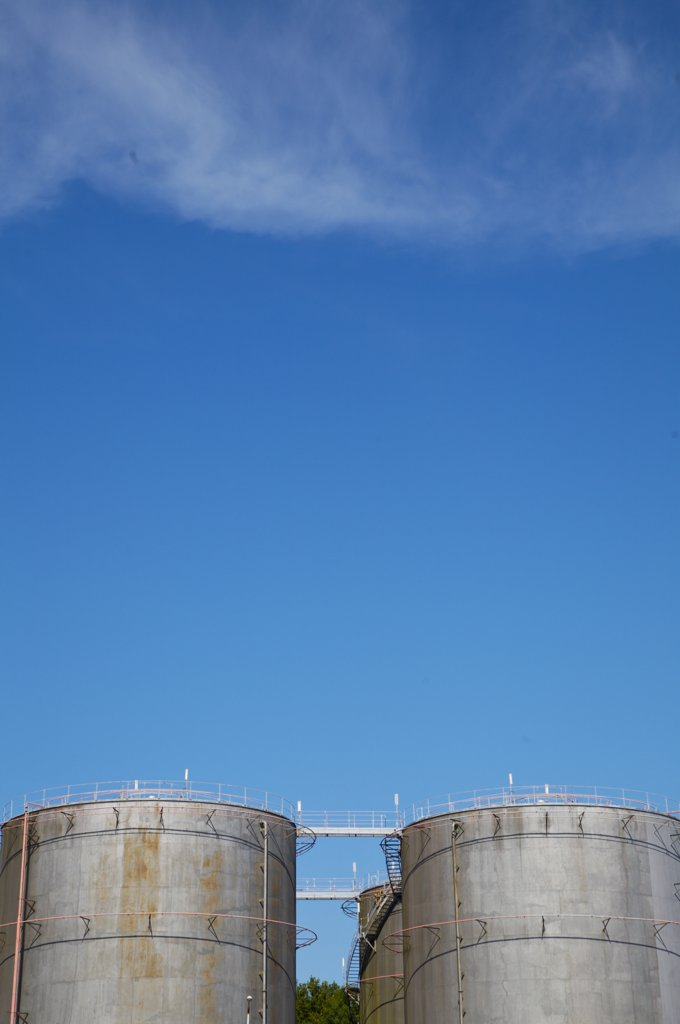 Industrial storage tanks against blue sky : Stock Photo