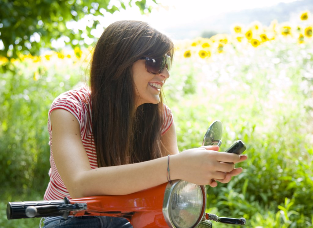 Stock Photo: 4278-1385 Portrait of a woman sitting on scooter and texting on cell phone