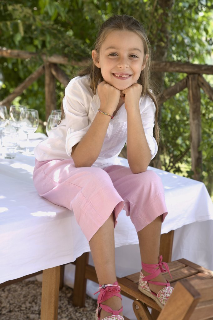 Stock Photo: 4278-1411 Portrait of a girl sitting on table