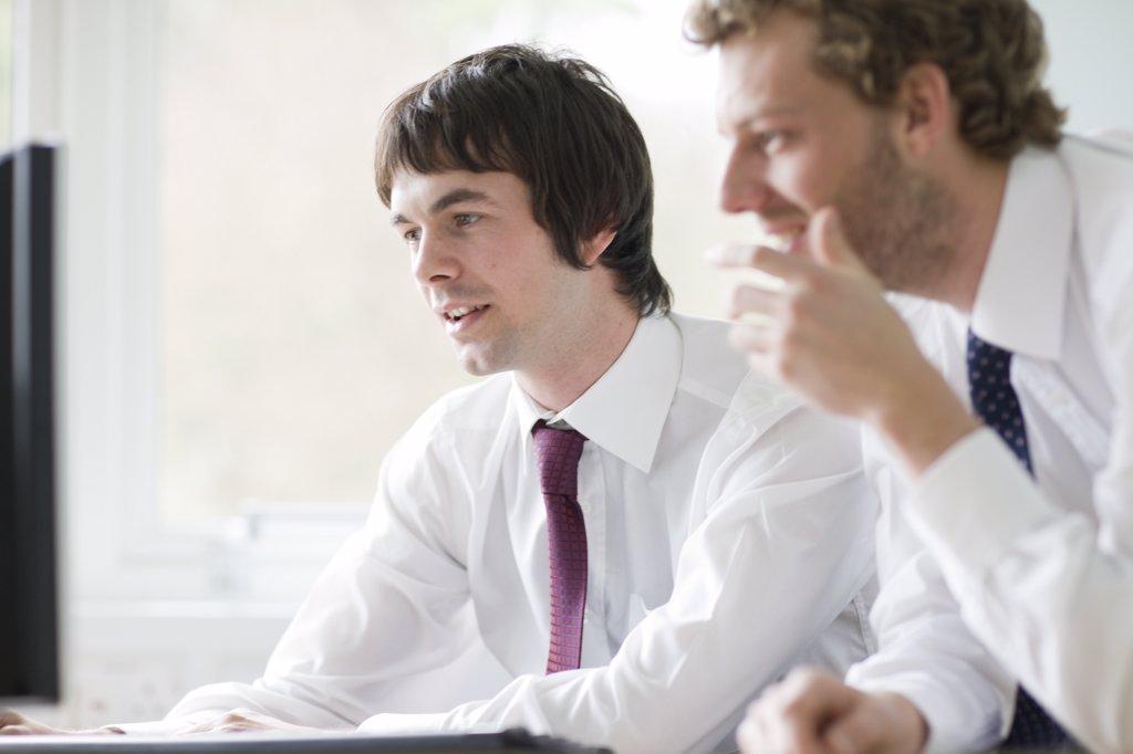 Stock Photo: 4278-2273 Two young businessmen leaning on desk