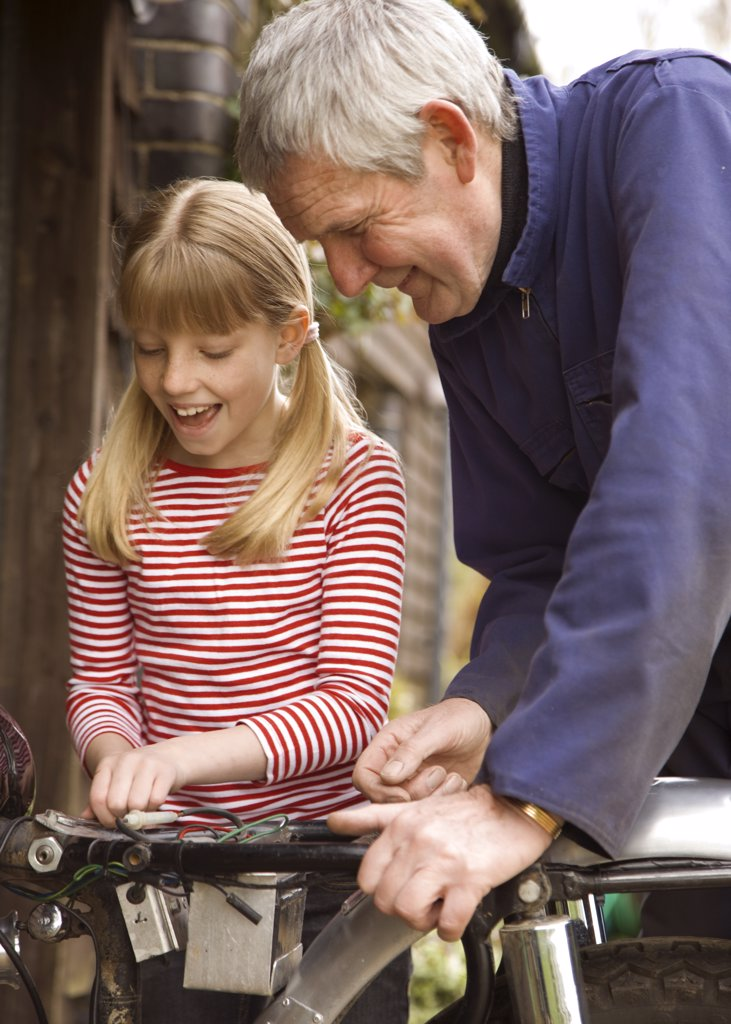 Young girl helping grandfather repairing motorbike : Stock Photo