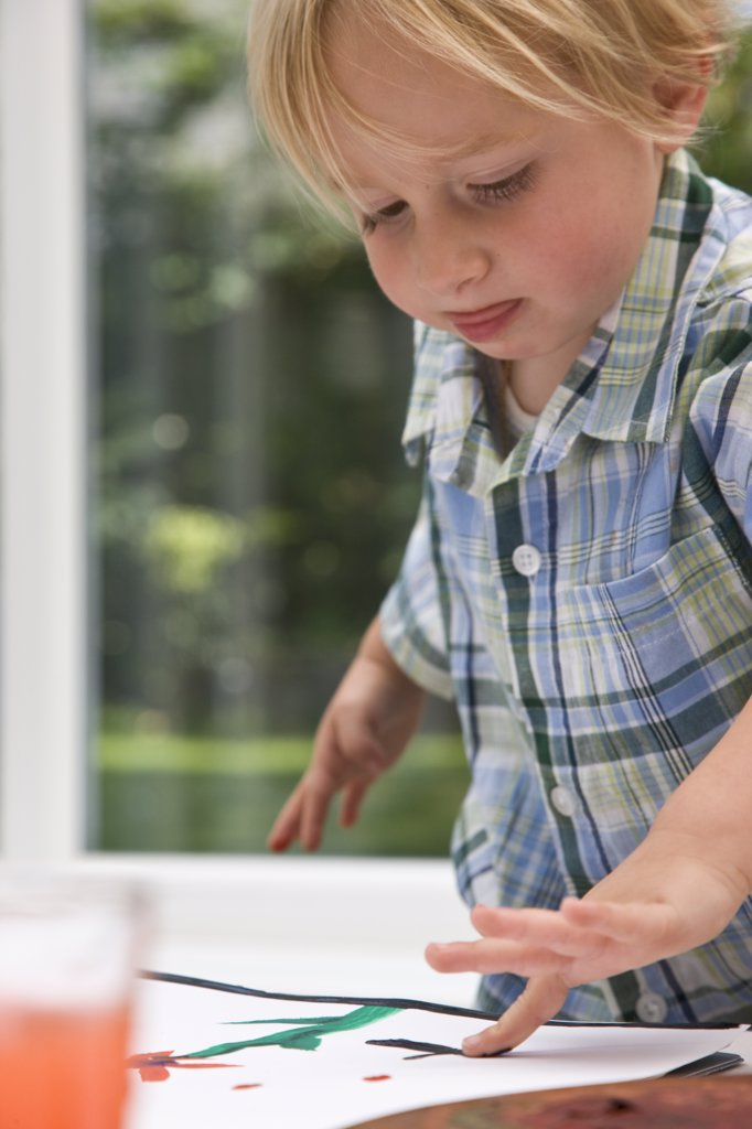 Stock Photo: 4278-2678 Portrait of a boy painting with finger