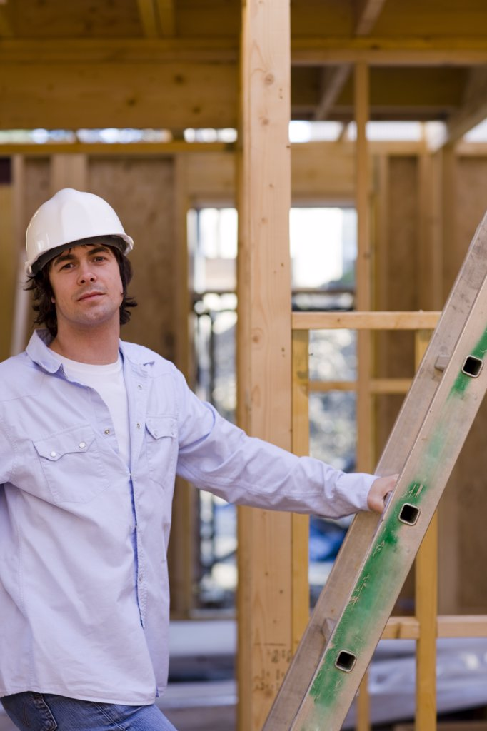 Stock Photo: 4278-2898 Portrait of a man climbing a ladder at construction site
