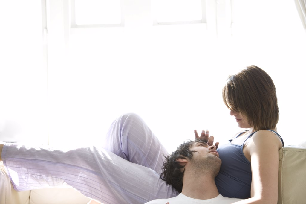 Stock Photo: 4278-2957 Couple talking and looking at each other with woman lying on sofa