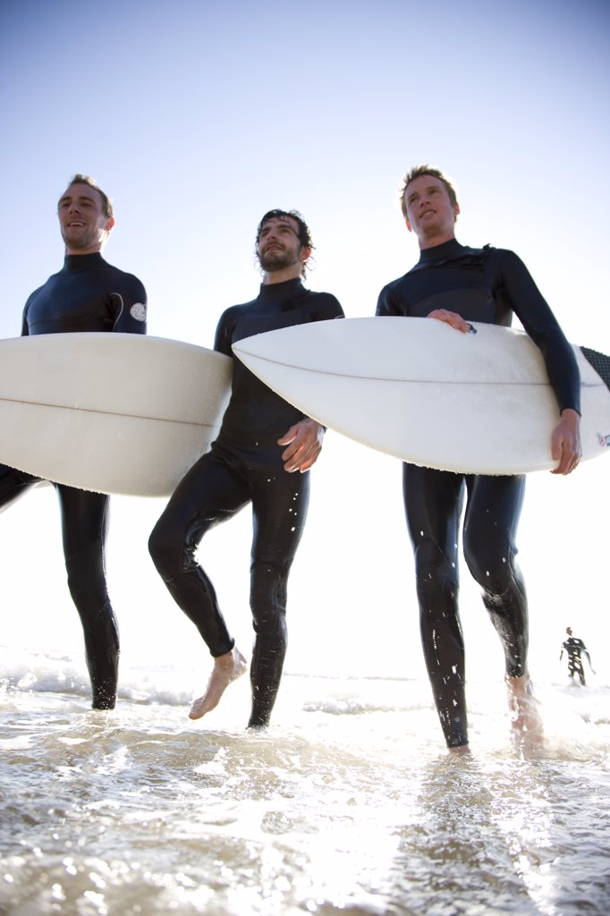 Three surfers walking out of the sea holding surfboards : Stock Photo