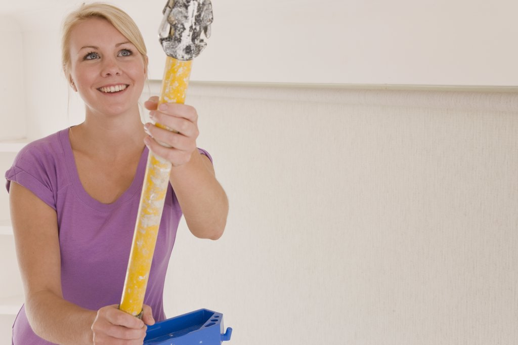Stock Photo: 4278-3326 Close up of smiling woman holding an extending paint roller