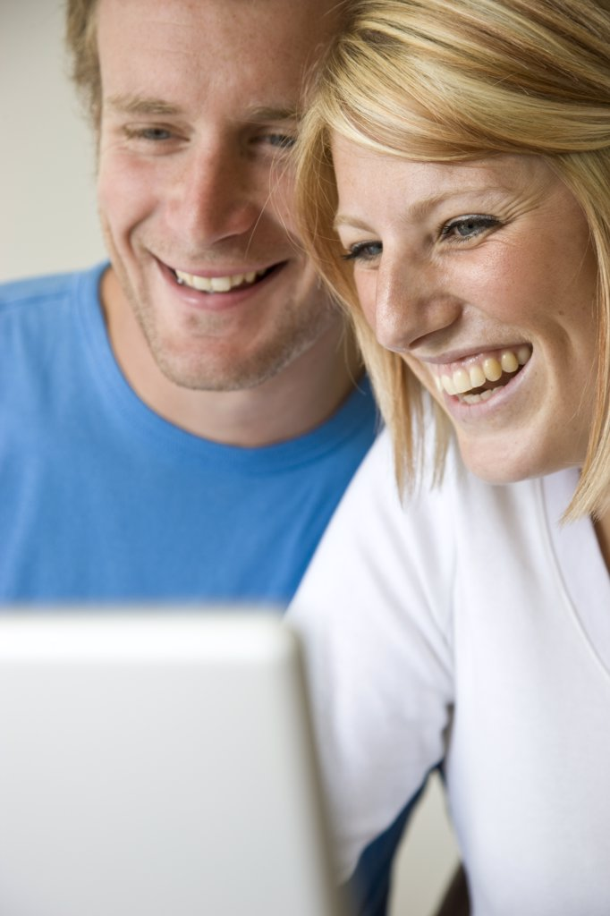 Stock Photo: 4278-3354 Close up of a couple laughing and looking at laptop computer screen