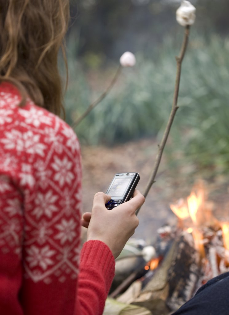 Back view of teenaged girl roasting marshmallow over campfire using cell phone : Stock Photo