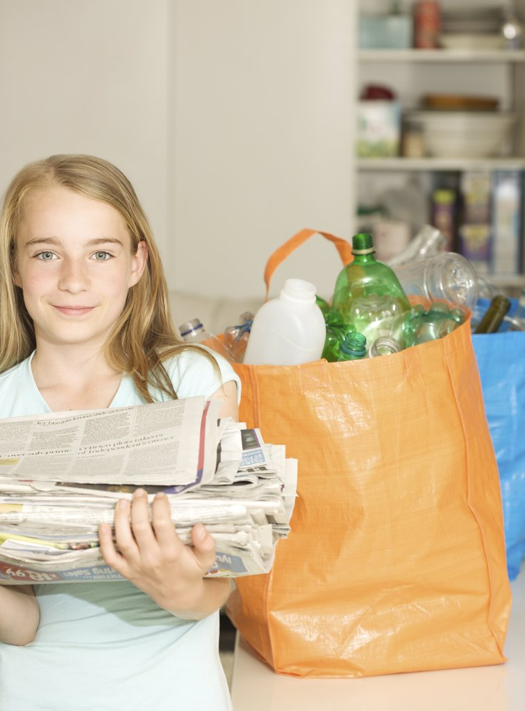 Stock Photo: 4278-3516 Young girl standing next to recycling bags holding a pile of newspapers