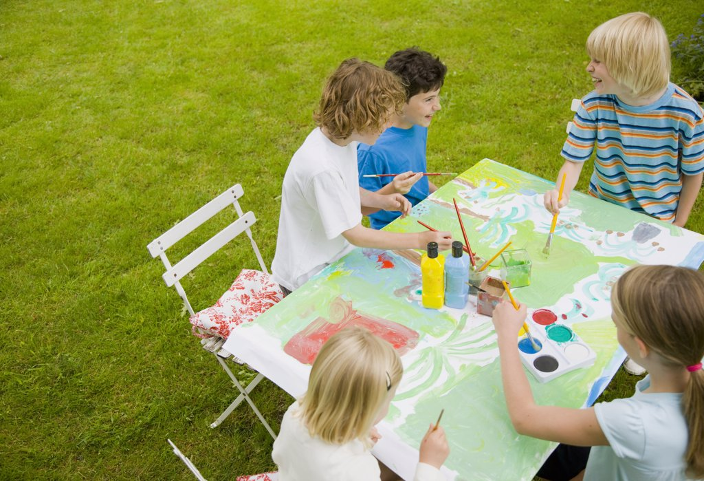 Children sitting and painting in the garden : Stock Photo