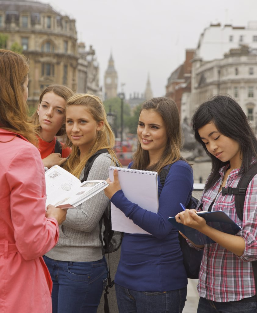 Back View of Woman Standing in front of Teenage Girls : Stock Photo