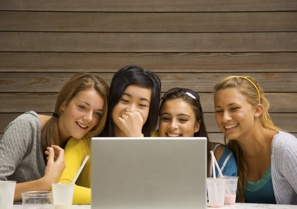 Stock Photo: 4278-3956 Teenage girls sitting in front of laptop computer laughing