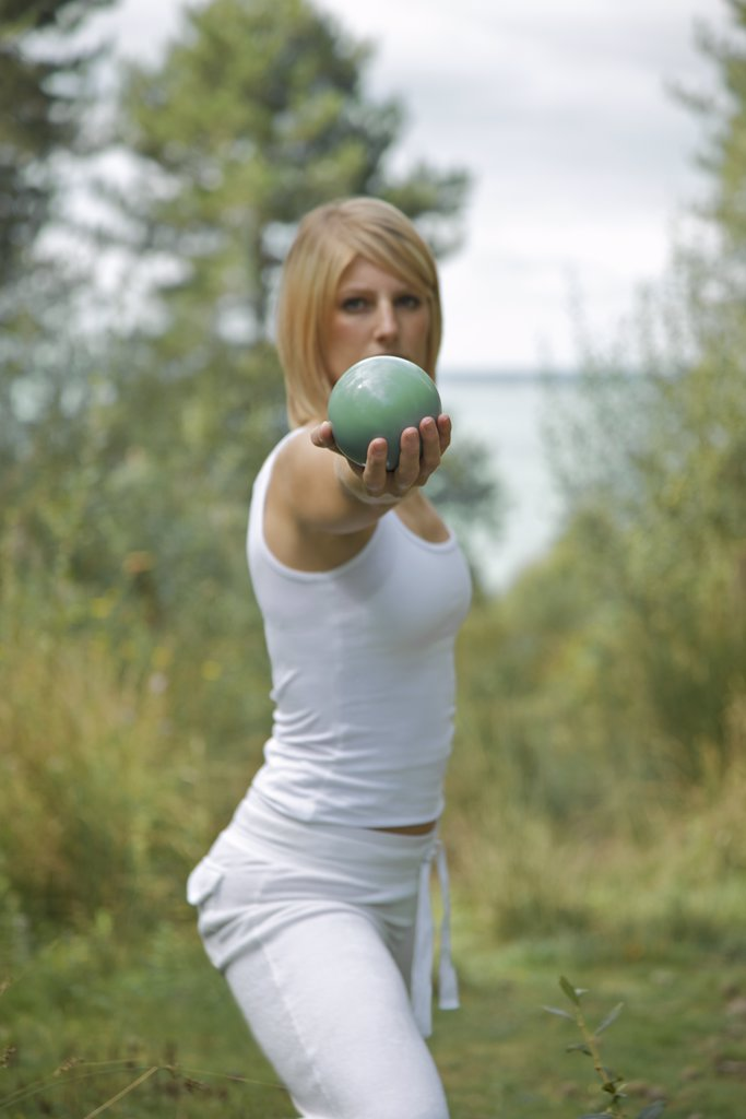 Young woman stretching and balancing a sphere in one hand : Stock Photo