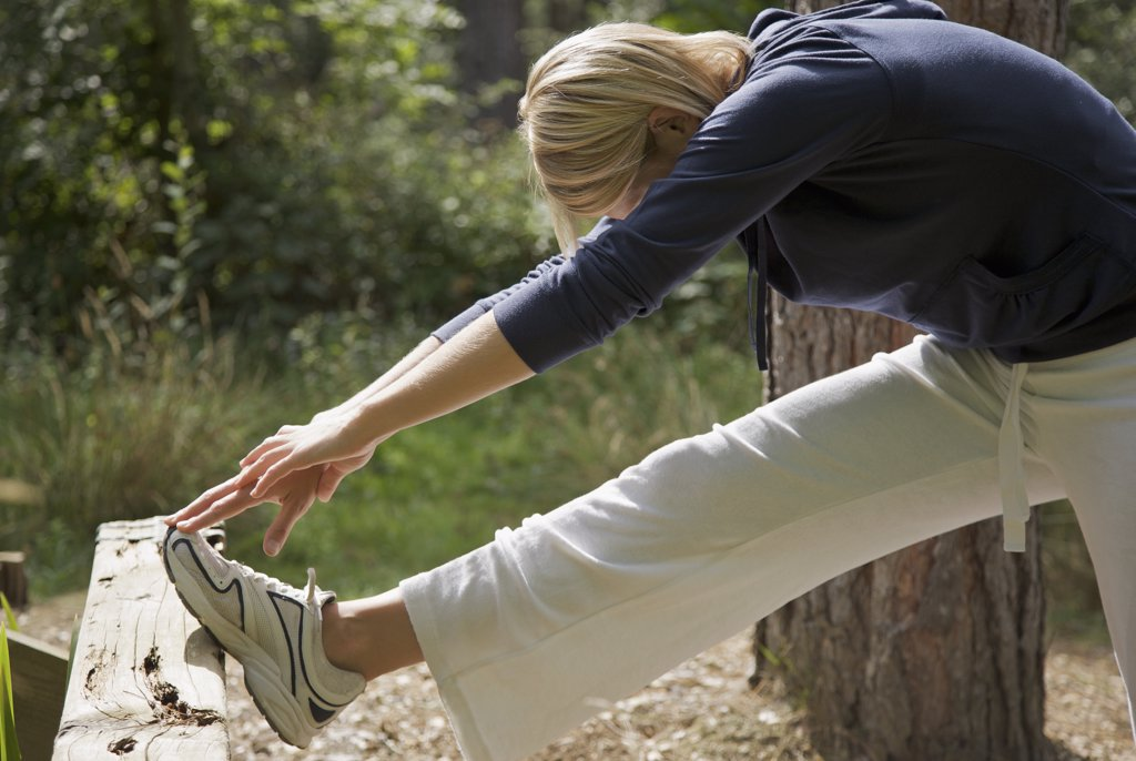 Stock Photo: 4278-3976 Young woman in a forest stretching her leg over a wooden beam and touching her foot