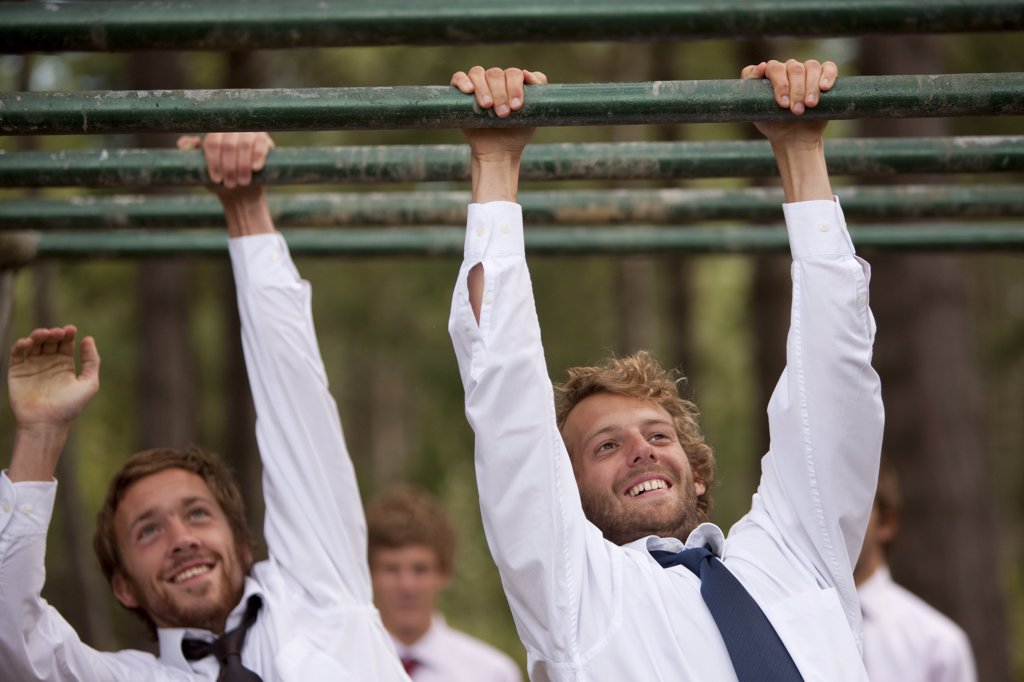 Stock Photo: 4278-3985 Two businessmen at an obstacle course dangling from parallel bars