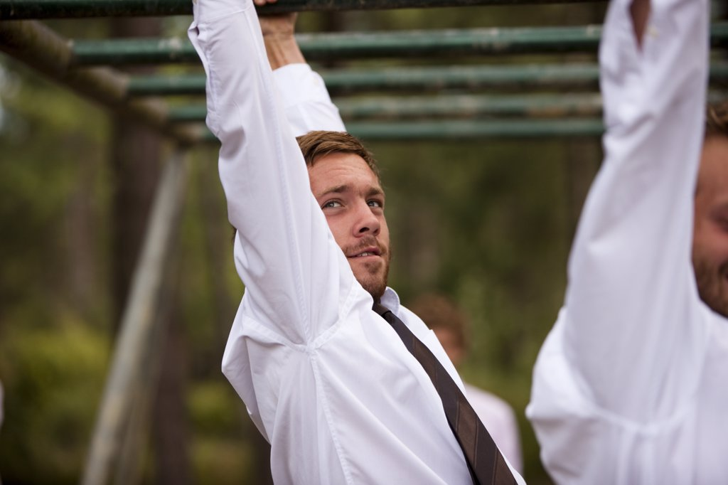 Stock Photo: 4278-3986 Businessman at an obstacle course dangling from parallel bars