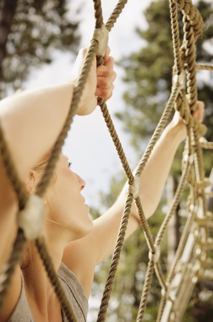 Stock Photo: 4278-3993 Young woman at obstacle course climbing a cargo net