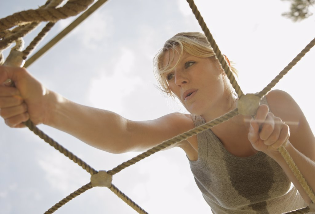 Stock Photo: 4278-3996 Young woman at obstacle course climbing a cargo net