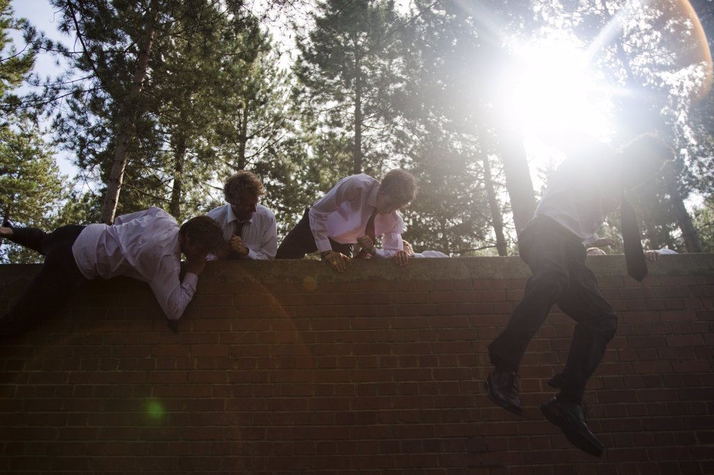 Businessmen at an obstacle course climbing a brick wall : Stock Photo