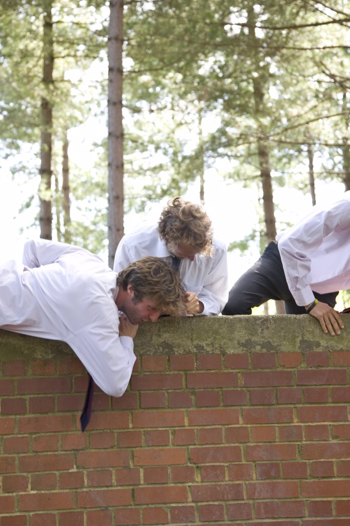 Stock Photo: 4278-4000 Businessmen at an obstacle course climbing a brick wall