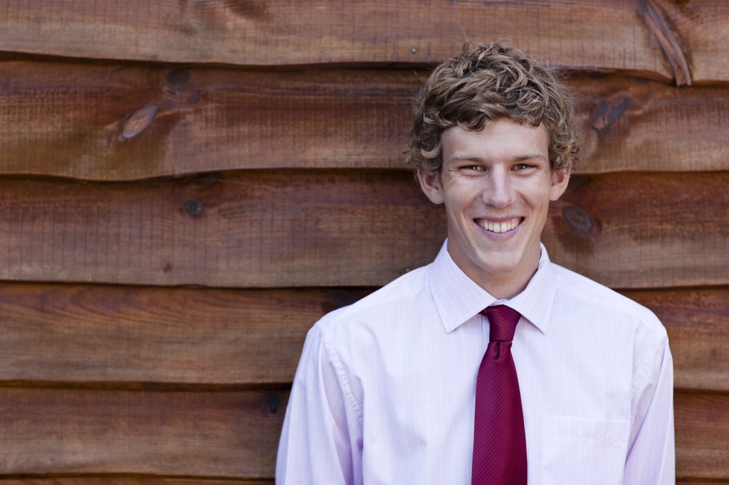 Stock Photo: 4278-4010 Young businessman standing against a wood wall
