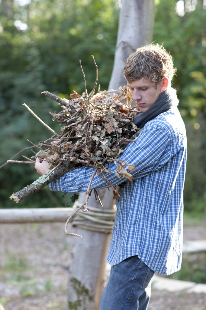 Stock Photo: 4278-4047 Young man carrying firewood
