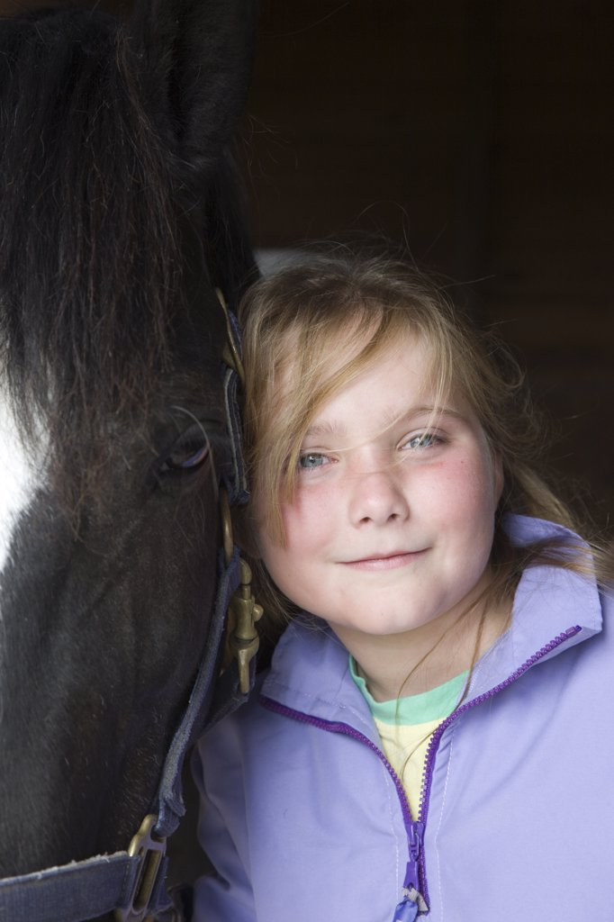 Young girl hugging a horse head : Stock Photo