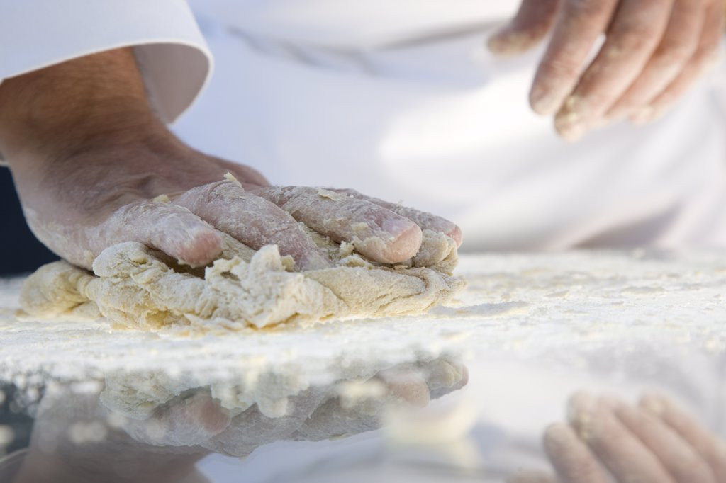Stock Photo: 4278-4393 Close up of a chef hands kneading pasta dough over a glass table