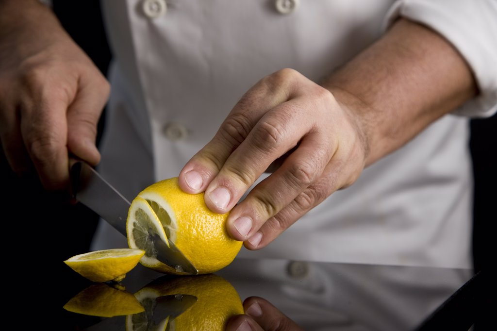 Stock Photo: 4278-4474 Close up of a chef hands slicing a lemon