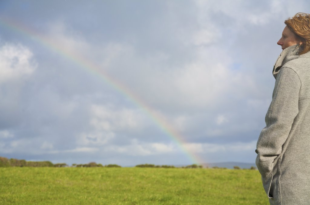 Woman standing in a field looking at the rainbow : Stock Photo